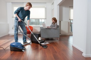 Man is vacuum cleaning while his girlfriend is working on the couch